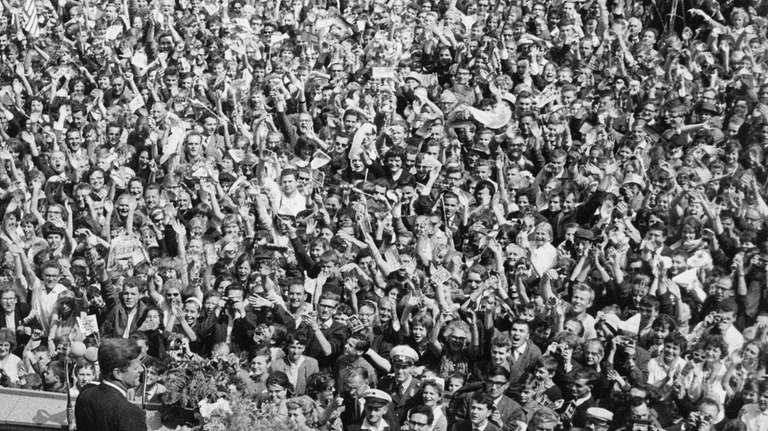 President John F. Kennedy is cheered by crowds