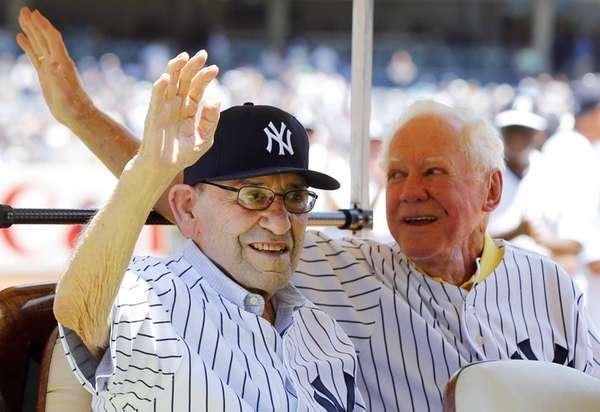 Yogi Berra, left, and Whitey Ford wave to