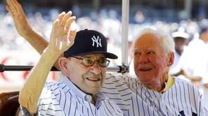 Yogi Berra, left, and Whitey Ford wave to