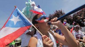Arianna Nazario, 9, of Massapequa, blows a horn