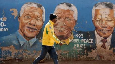 A man walks past a mural depicting different
