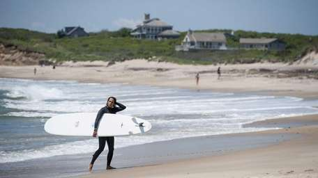 A woman exits the water after surfing at