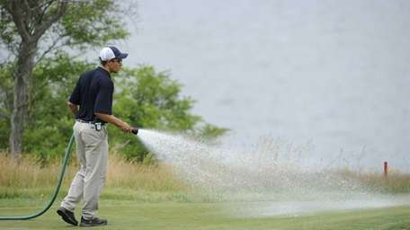 A groundskeeper waters a fairway on Wednesday at