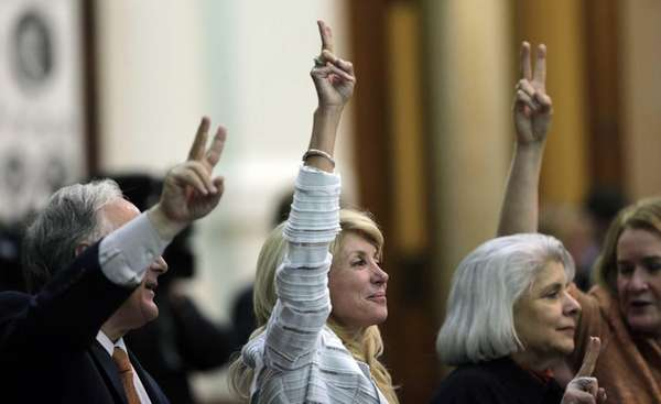 Sen. Wendy Davis, center, holds up two fingers
