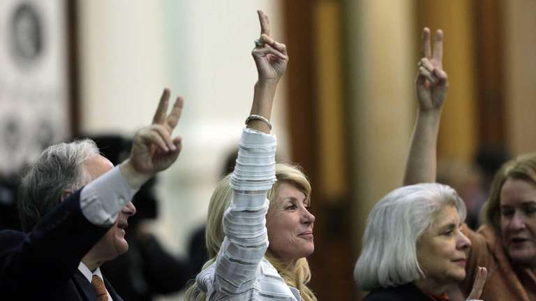Sen. Wendy Davis, center, holds up two fingers