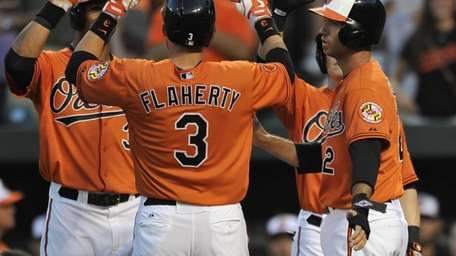 Baltimore Orioles' Ryan Flaherty is congratulated by teammates