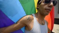 A man waves a rainbow flag during the