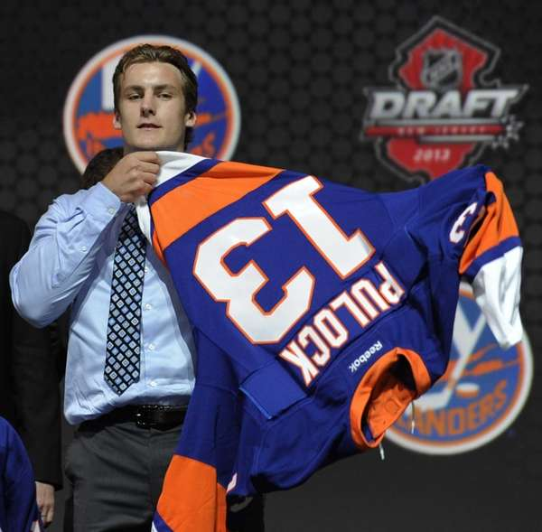 Defenseman Ryan Pulock pulls on an Islanders sweater