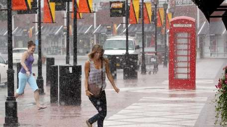 Shoppers seek cover from a Monday afternoon downpour