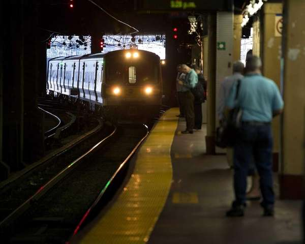 LIRR commuters wait on a platform at Penn