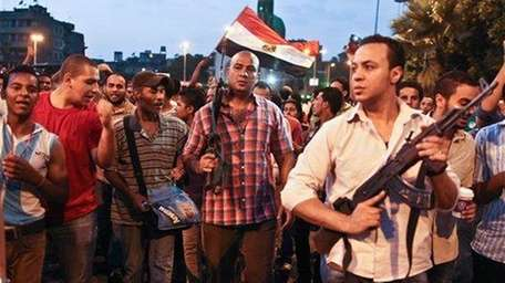 Plainclothes policemen walk with protesters opposed to Egyptian
