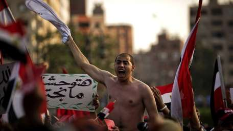 An Egyptian opposition protester shouts slogans as tens