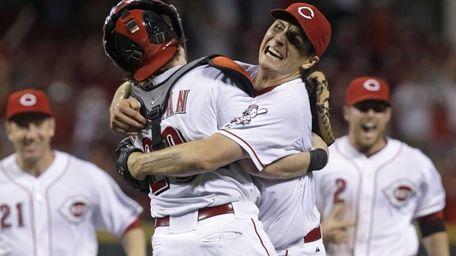 Cincinnati Reds starting pitcher Homer Bailey, right, hugs