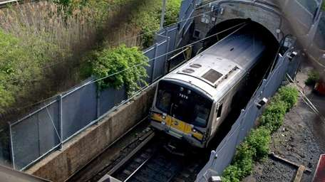 An LIRR train disappears into a tunnel westbound