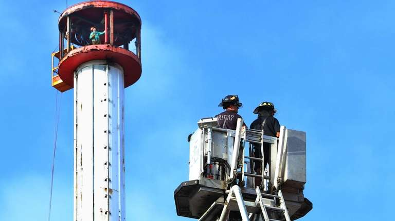 Firemen look on as workers disassemble the Astrotower