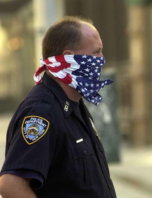 An NYPD officer covers his mouth with a