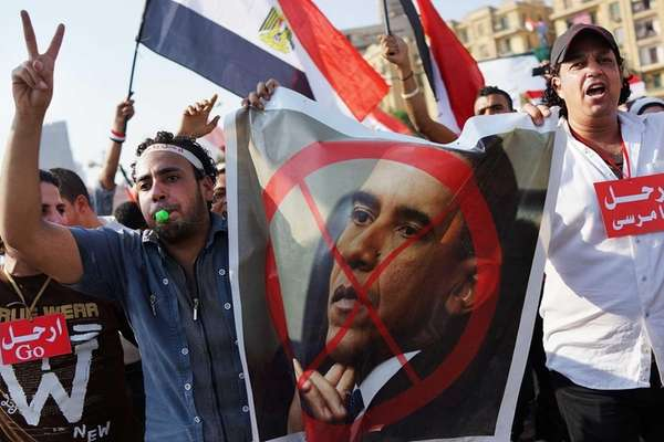 Protesters carry anti-Obama posters as thousands of Egyptians