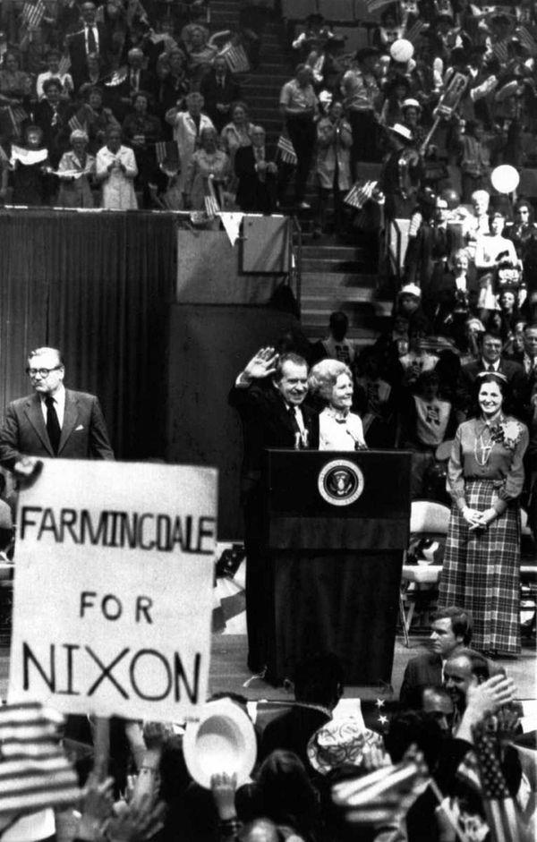Standing with Mrs. Nixon, President Richard Nixon acknowledges