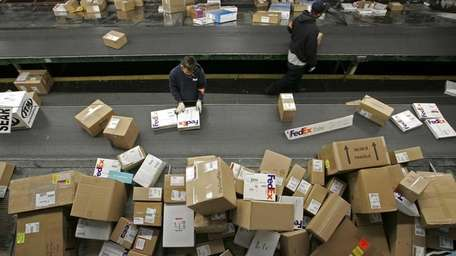 A FedEx worker sorts packages being uloaded from