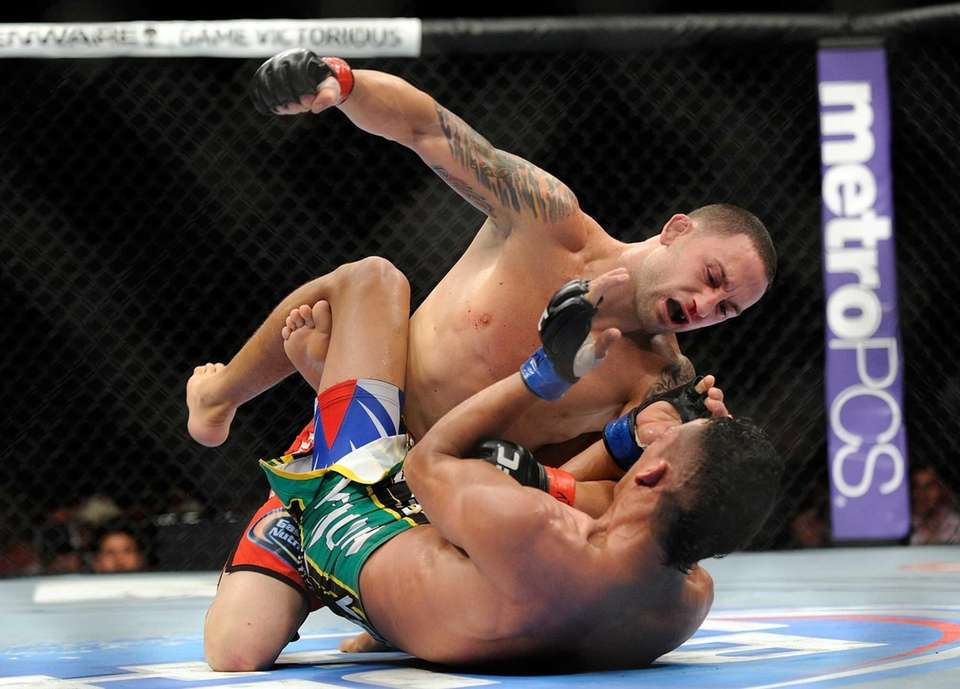 Frankie Edgar punches Charles Oliveira during their UFC