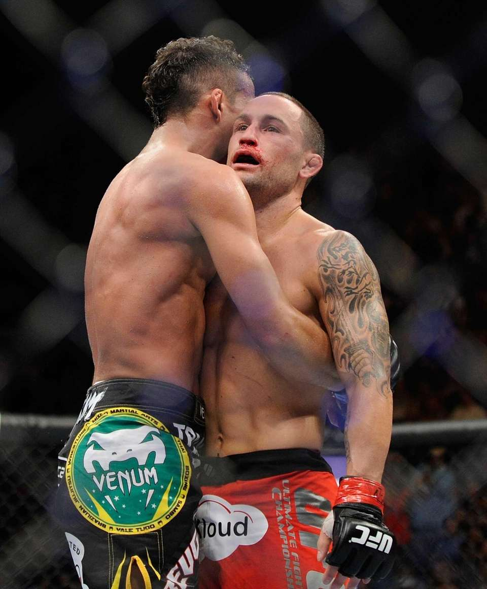 Frankie Edgar, right, is hugged by Charles Oliveira