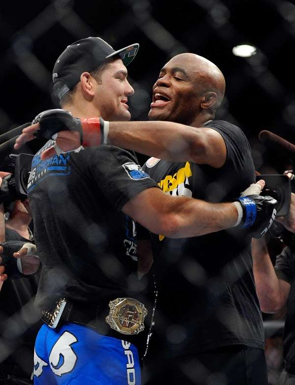 Chris Weidman, left and Anderson Silva embrace after