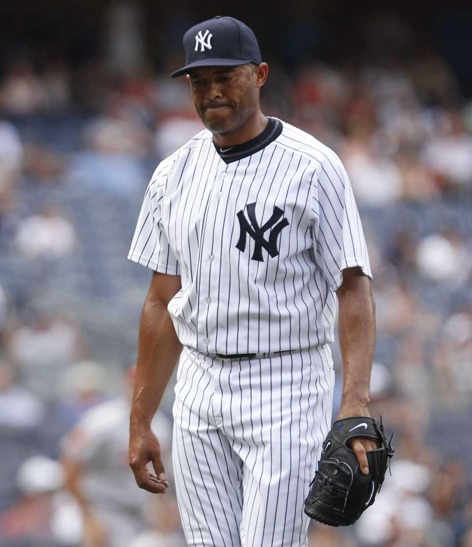 Yankees relief pitcher Mariano Rivera walks off the