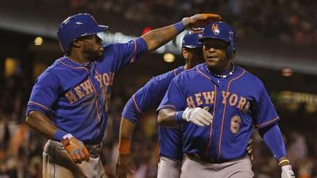 Marlon Byrd, right, is greeted by teammate Eric
