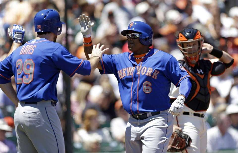 Marlon Byrd, center, is greeted by Ike Davis,
