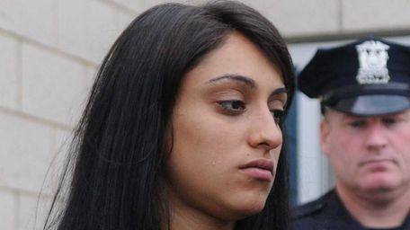 Marissa Kovalovsky, 19, of Selden, is led out