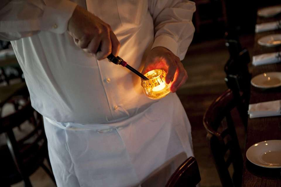 A waiter lights a candle at Fresh Hamptons