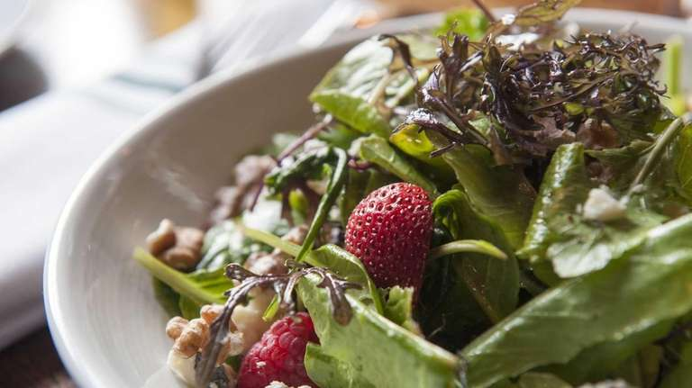 A mixed berry salad is served with mesclun