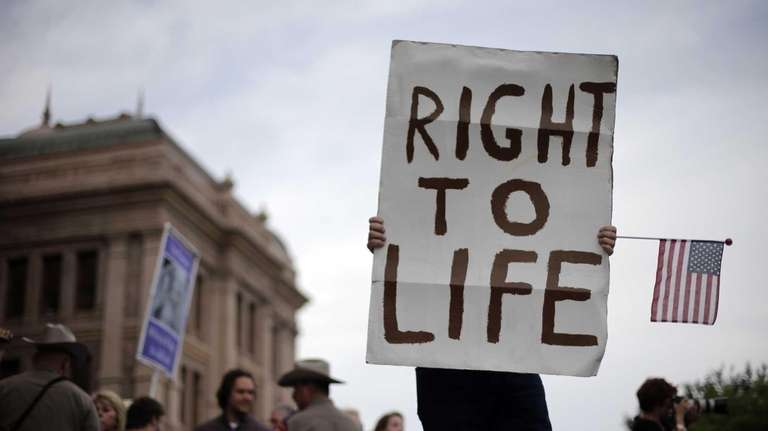 A man holds a sign during an anti-abortion
