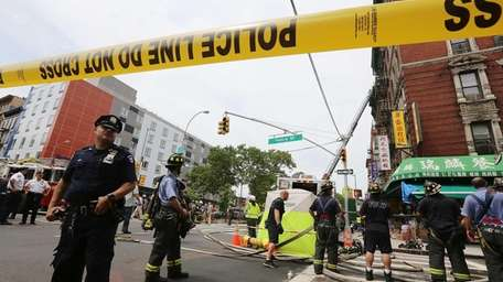Firefighters and police gather at the scene of