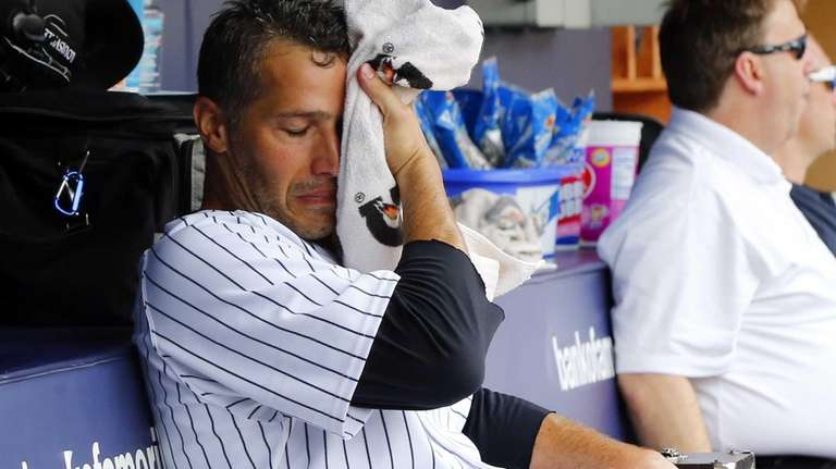 Andy Pettitte sits in the dugout after leaving