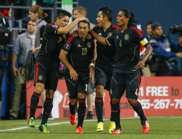 Marco Fabian (#10) of Mexico celebrates with teammates
