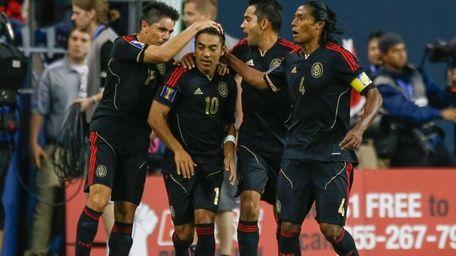 Marco Fabian (#10) of Mexico celebrates with teammates