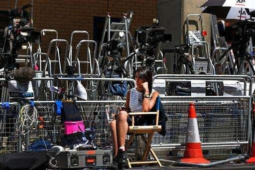 A journalist sits among stepladders and camera equipment
