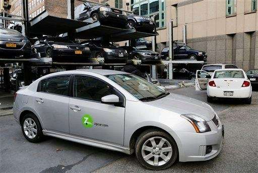 A Zipcar is parked at a lot in