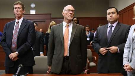 George Zimmerman stands with his defense team, Mark