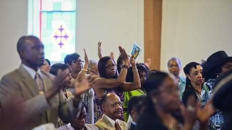 Parishioners pray and applaude as the community listens