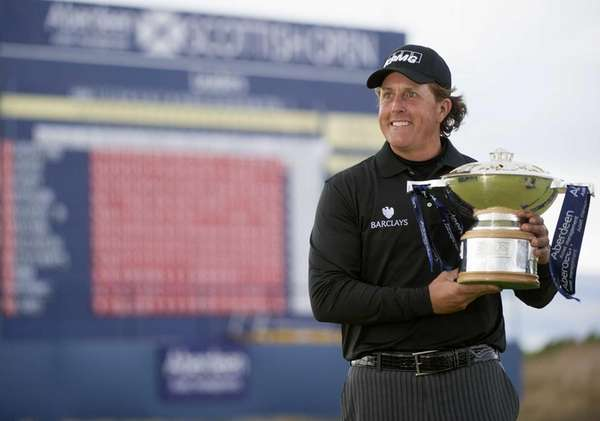 Phil Mickelson poses with the trophy after winning