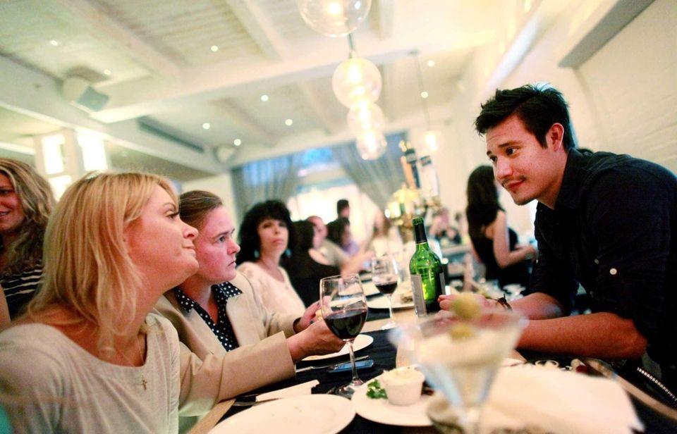 Bartender Jose De La Rosa chats with customers