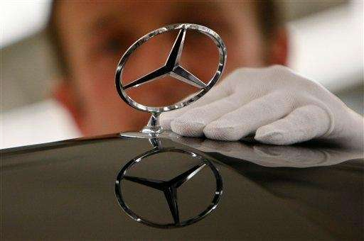 A worker fixes the Mercedes logo on to