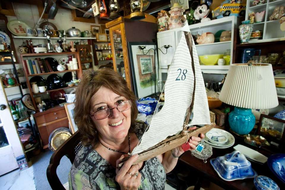 Lynn Musa holds a handcrafted sailboat that she