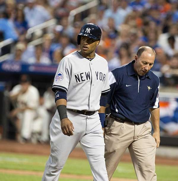 American League's Robinson Cano leaves the game after