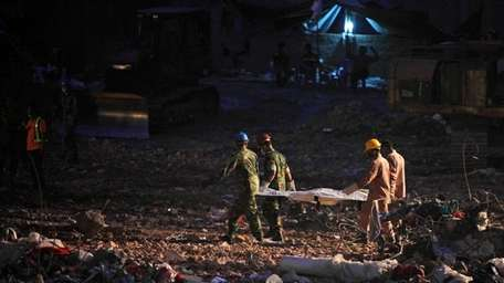 Rescuers carry the body of a victim retrieved