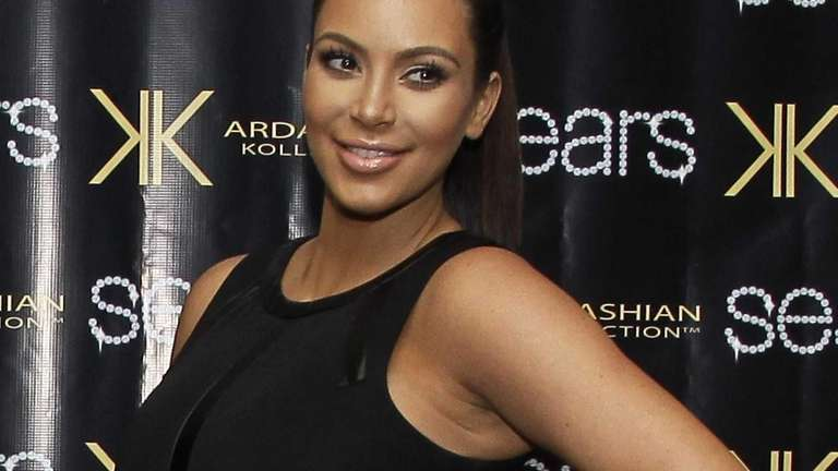 Kim Kardashian signs autographs for fans during a