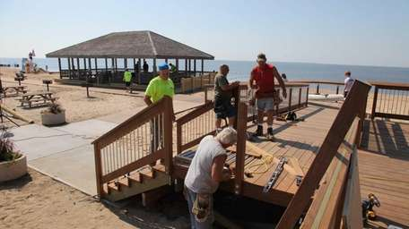 Workers complete work on a railing that had