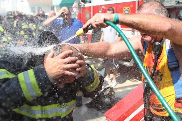 A Long Beach firefighter is hosed down after